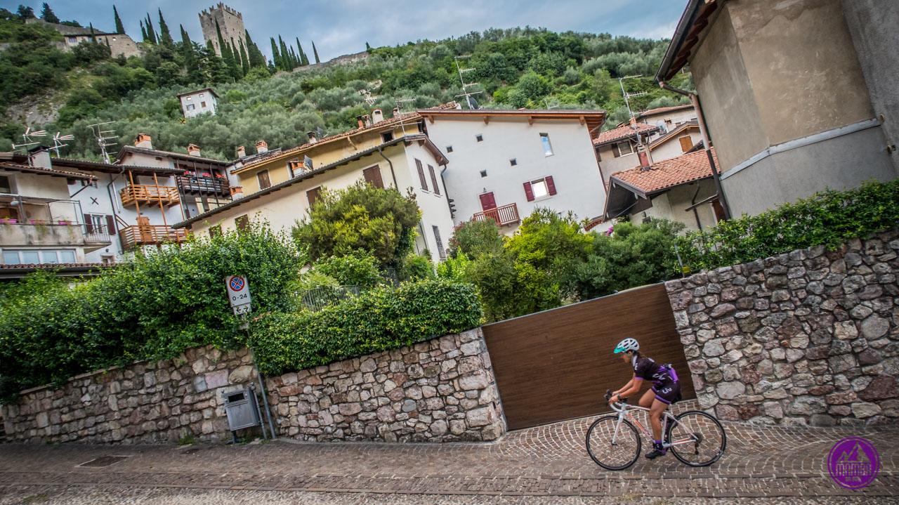 Kobieta na rowerze szosowym we włoskim miasteczku.
